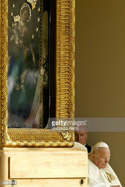 Pope John Paul II is taken past a painting of Madonna del Rosario as he makes his way to pray for world peace at the shrine of Virgin Mary in Pompei...
