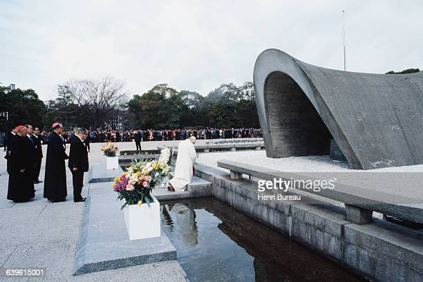 Pope John Paul II kneels before the flame of the cenotaph honoring the victims of the atomic bomb in Hiroshima