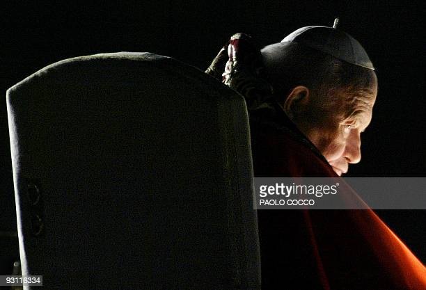 Pope John Paul II looks on from the Palatine Hill during the Stations of the Cross ceremony in Rome 18 April 2003 The 82yearold pontiff this year...