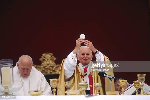 Pope John Paul II raises the host as he performs Holy Communion