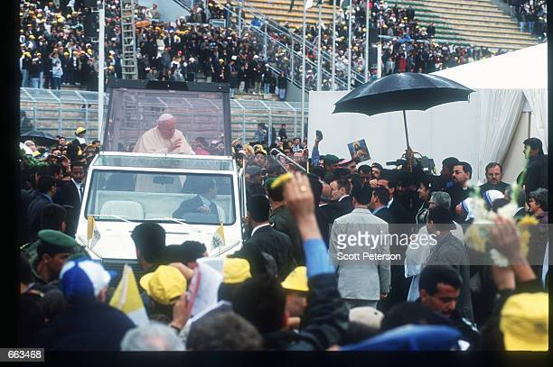 Pope John Paul II rides in the Popemobile while he waves to a crowd March 21 2000 at the Sport City Stadium in Amman Jordan He is the first Roman...