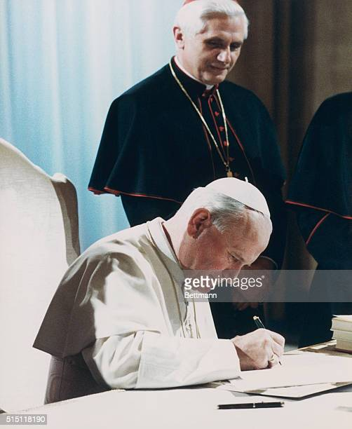 Pope John Paul II signs the new Roman Catholic Code of Canon Law Cardinal Joseph Ratzinger looks over Pope's shoulder