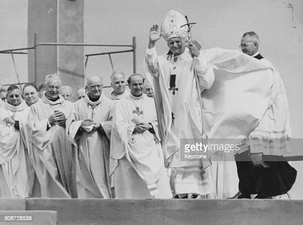 Pope John Paul II standing on stage raising his arms as he blesses the crowd during a mass in Le Bourget June 1st 1980