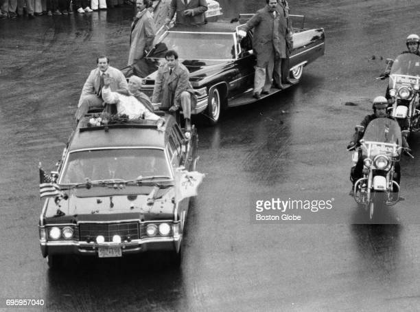 Pope John Paul II surrounded by Secret Service agents waves to several thousand spectators from an open car at Edward Everett Square in Dorchester...
