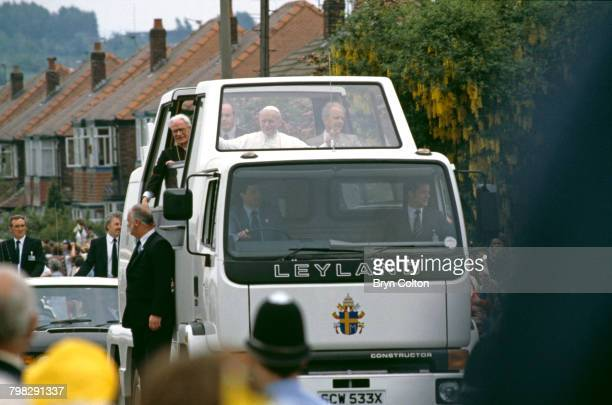 Pope John Paul II waves from the popemobile as he travels through crowds lining the street on his way to conduct an openair mass at Heaton Park...