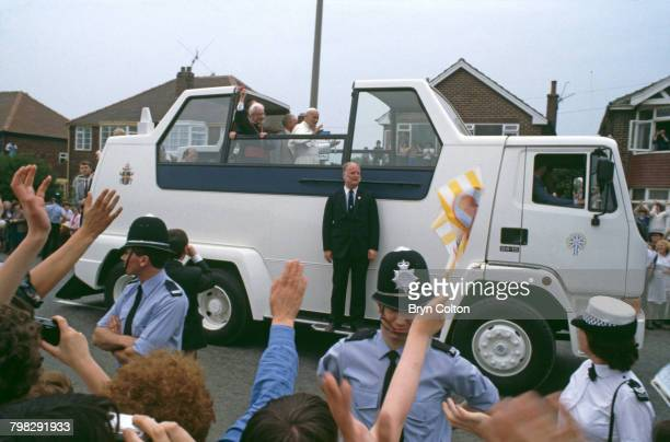 Pope John Paul II waves from the popemobile as he travels through crowds lining the street on his way to conduct an open-air mass at Heaton Park,...