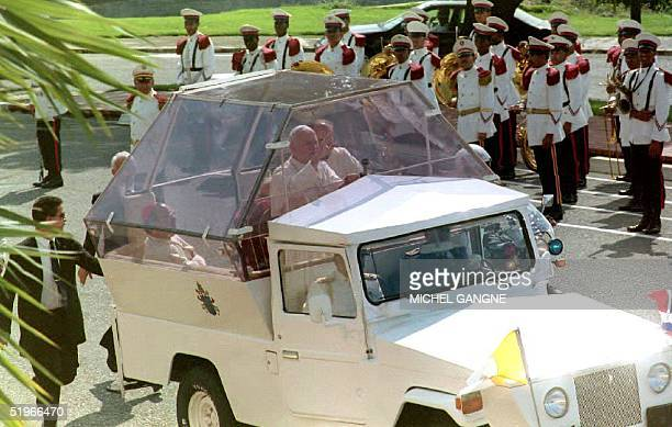 Pope John Paul II waves to people gathered outside the gates of the Presidential Palace in Santo Domingo 10 October 1992 as he arrives to meet with...