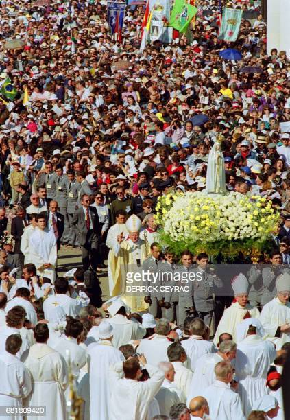 Pope John Paul II waves to the cheering crowd 12 May 1991 as he walks behind the statue of the Virgin of Fatima prior to celebrates a mass in the...