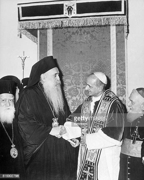 Pope Paul VI and Patriarch Athenagoras I shake hands as they meet in the Roman Catholic Apostolic Mass atop the Mount of Olives along with...