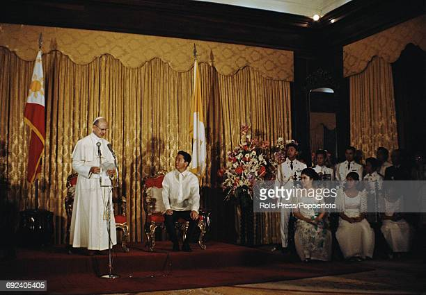 Pope Paul VI pictured reading an address to the seated President Ferdinand Marcos and assorted guests including Imelda Marcos during a pastoral visit...