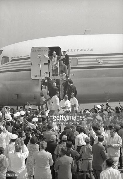 Pope Paul VI still on the steps of the DC8 Alitalia 'Emanuele Possagno' just landed at Fiumicino Airport greets the rushing crowd with a wide gesture...