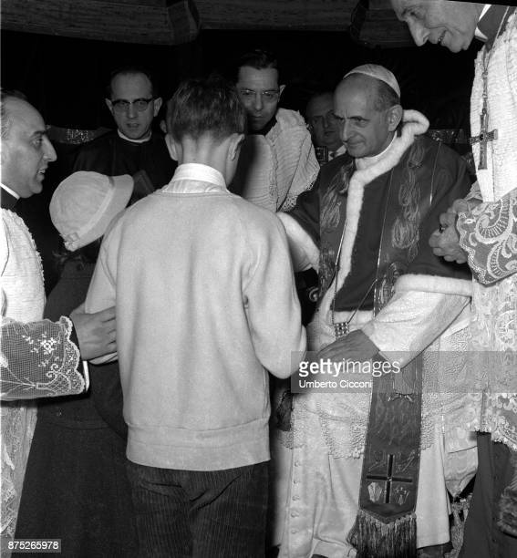 Pope Paul VI talks to a young boy during the celebration of Mass in St Peter's Basilica in 1964