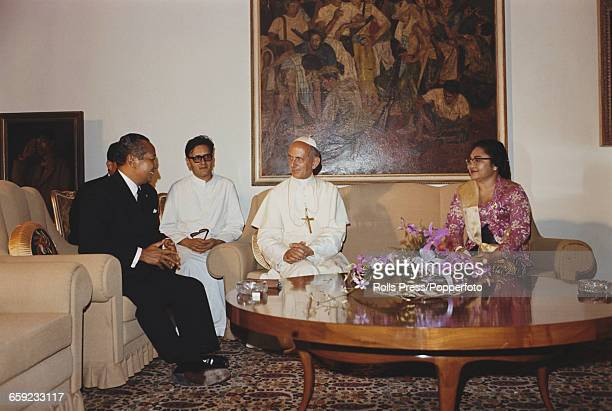 Pope Paul VI talks with President Suharto of Indonesia and his wife Siti Hartinah in Jakarta after arriving on a flight from Australia during the...