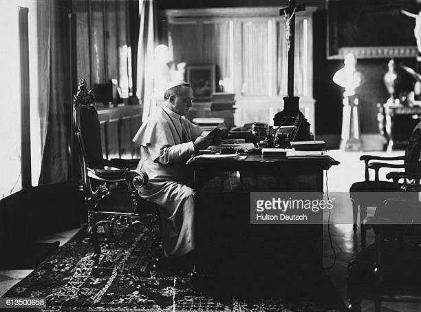 Pope Pius XI sits at a desk and reads He was born in 1857 and died in 1939 and was Pope from 1922
