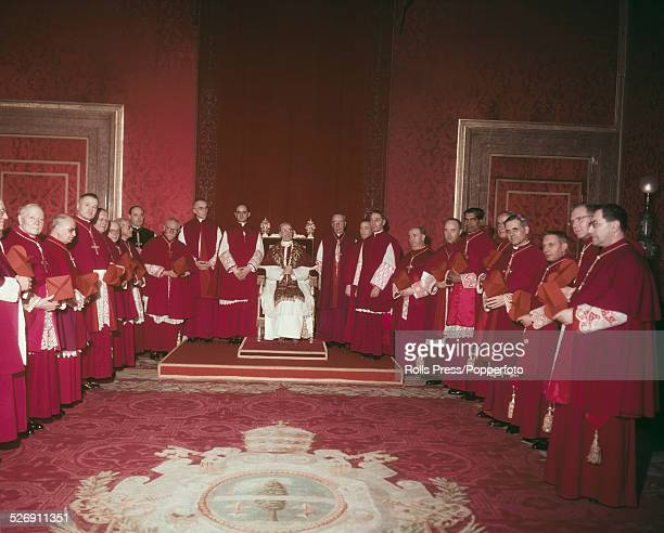 Pope Pius XII pictured with newly elevated cardinals in his throne room after presenting them with red berettas at the Vatican in Rome circa 1953...