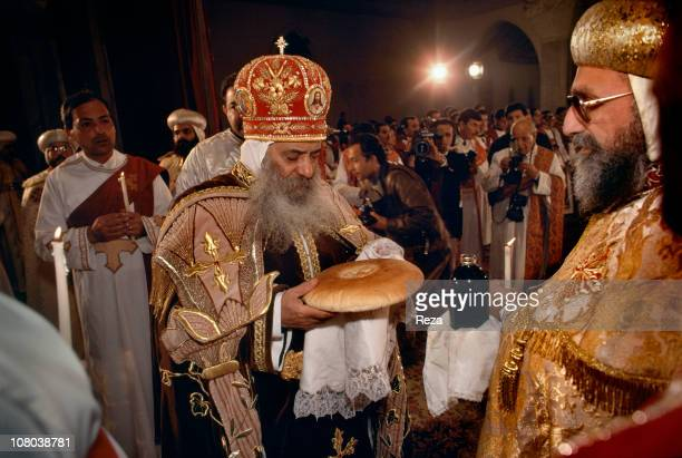 Pope Shenouda III breaks the bread during the Coptic Christmas ceremony celebrated in the Cathedral of St Mark in Cairo on the night of 6th to 7th...