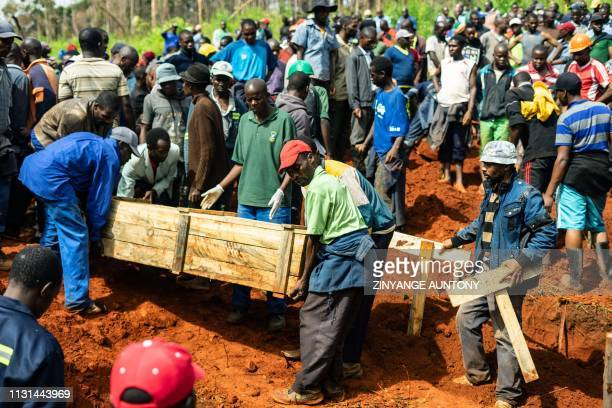 Popel carry coffins as mourners attend multiple burials at the Chimanimani Heroes Acre on March 18 2019 in Chimanimani eastern Zimbabwe after the...
