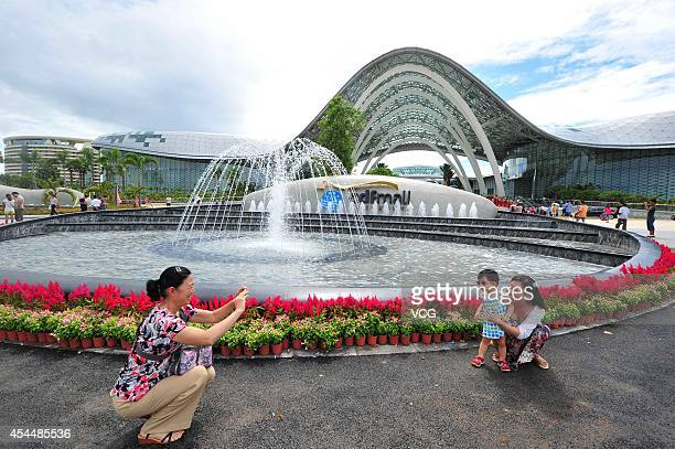 Popele take photos near the world's largest dutyfree shop on Semptember 1 2014 in Sanya Hainan province of China The world's largest dutyfree shop...