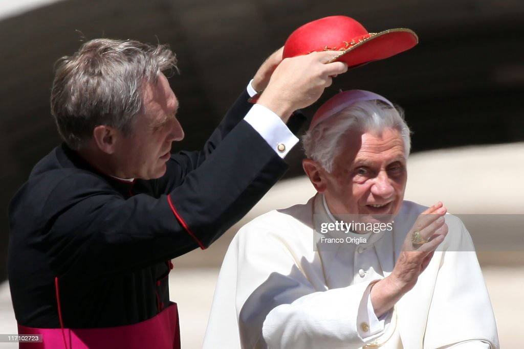 Pope's personal secretary Georg Ganswein adjusts Pope Benedict XVI's 'Saturno' (pontiff's hut) as they arrive at St. Peter's square for the weekly audience on June 22, 2011 in Vatican City, Vatican. The Vatican announced yesterday that at the end of the year Pope Benedict XVI will receive a new hybrid Popemobile.