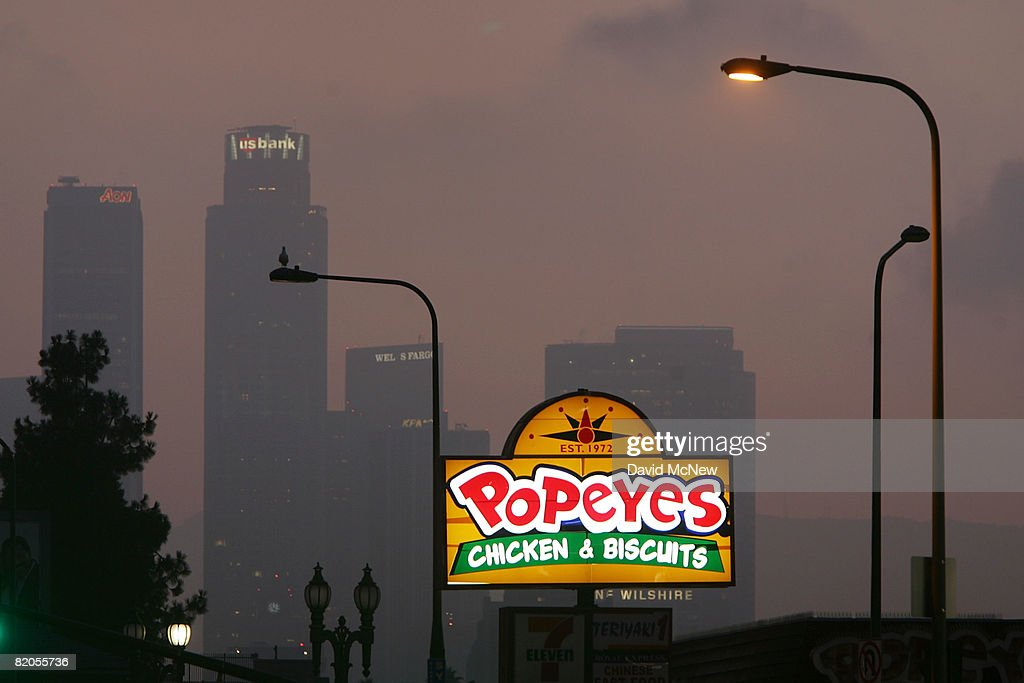 A Popeyes Fast Food Restaurant Sign Glows Above The City Skyline On July 24
