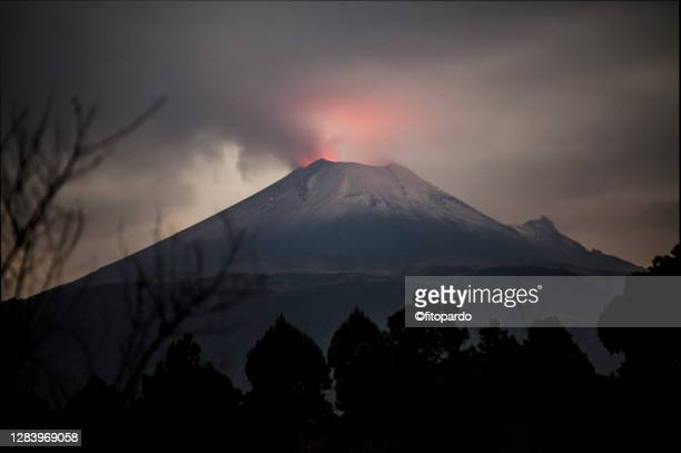 popocatepetl volcano in eruption at night with volcanic luminance over the cone - mexico stock pictures, royalty-free photos & images