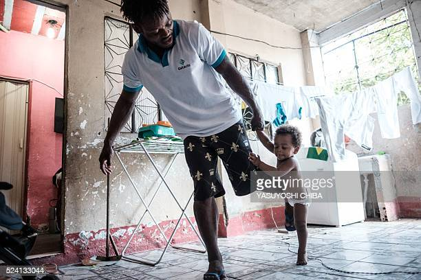 Popole Misenga a refugee judoka from the Democratic Republic of Congo, plays judo with his one-year-old son Heliasin at home in Rio de Janeiro,...