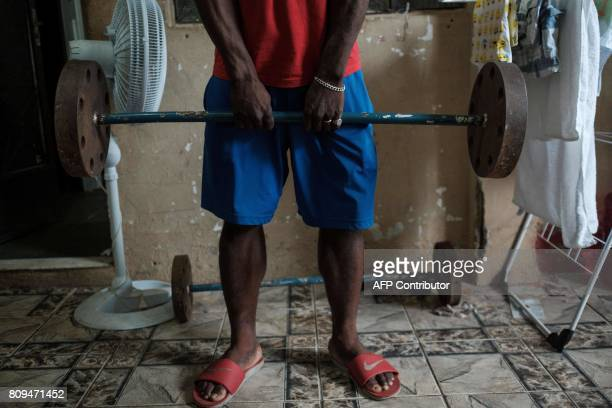 TOPSHOT Popole Misenga a refugee judoka from the Democratic Republic of Congo carries handmade 60kg weight at his home in Rio de Janeiro Brazil on...