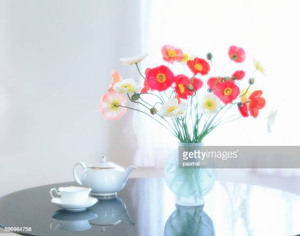 Poppies in vase next to tea pot and tea cup