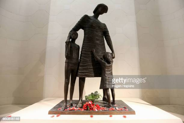 Poppies lie at the base of Lyndon Smith's statue 'Mother and Children' in the Hall of Memories during the Anzac Day Dawn Service at Pukeahu National...