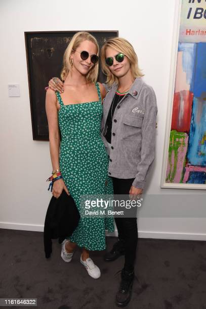 Poppy Delevingne and Cara Delevingne attend the Teen Cancer America Suite at Bob Dylan and Neil Young in Hyde Park on July 12, 2019 in London,...