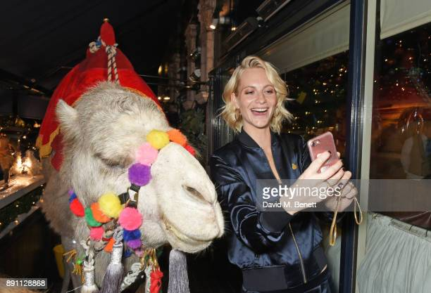 Poppy Delevingne takes a selfie with a camel at the Love x Chaos x Poppy Delevingne x Moet Christmas Party at George on December 12 2017 in London...