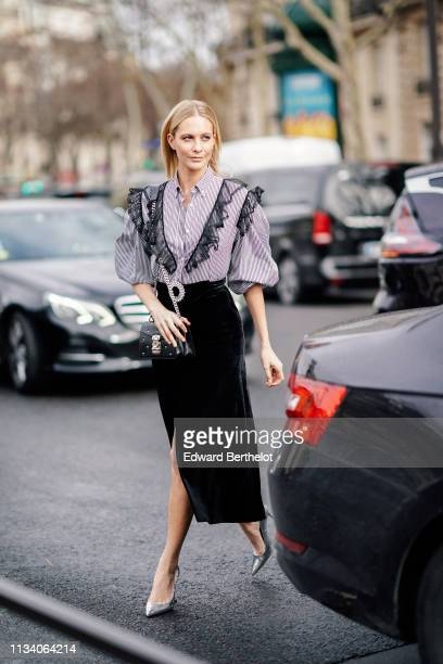 Poppy Delevingne wears a striped shirt with black lace, a black skirt, a belt, a bag, outside Miu Miu, during Paris Fashion Week Womenswear...