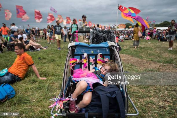 Poppy Woods sleeps in a pram whilst her parents watch Charli XCX on The Other Stage at Glastonbury Festival Site on Worthy Farm in Pilton on June 23...