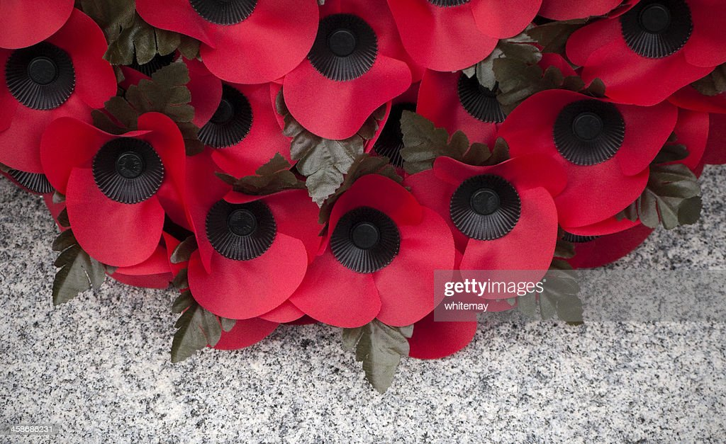 Poppy wreath on a stone war memorial : Stock Photo