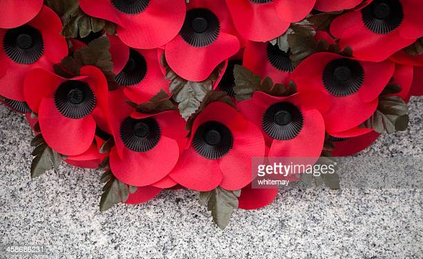 poppy wreath on a stone war memorial - armistice day stock photos and pictures