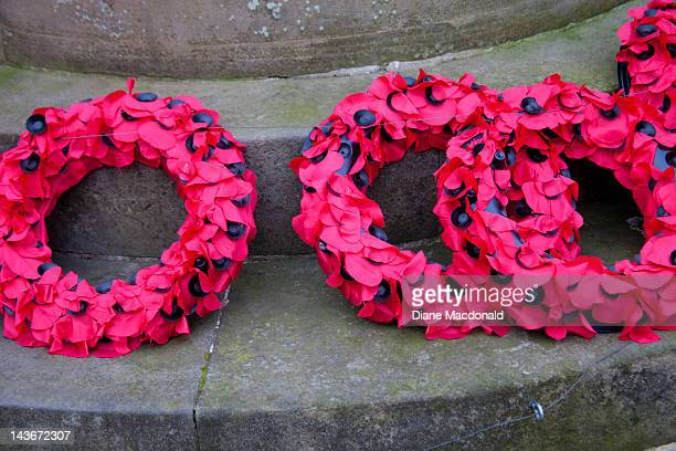 Poppy wreaths at the base of a war memorial