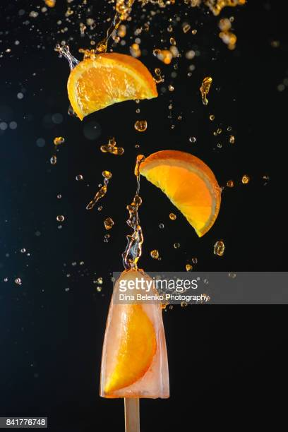 Popsicle with fresh orange slices on a dark background, dynamic shot with action, splash, water drops and bokeh.