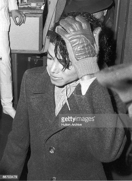Popular American musician Michael Jackson stands with a gloved hand on his head during the filming of the longform music video for his song 'Bad'...