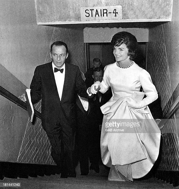 Popular American signer and actor Frank Sinatra escorts soon-to-be First Lady Jacqueline Kennedy up the stairs during a gala at the National Guard...