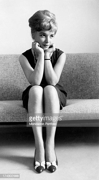 Popular announcer Aba Cercato smiling and welldressed sits on a sofa looking elsewhere with her chin on her hands June 1960
