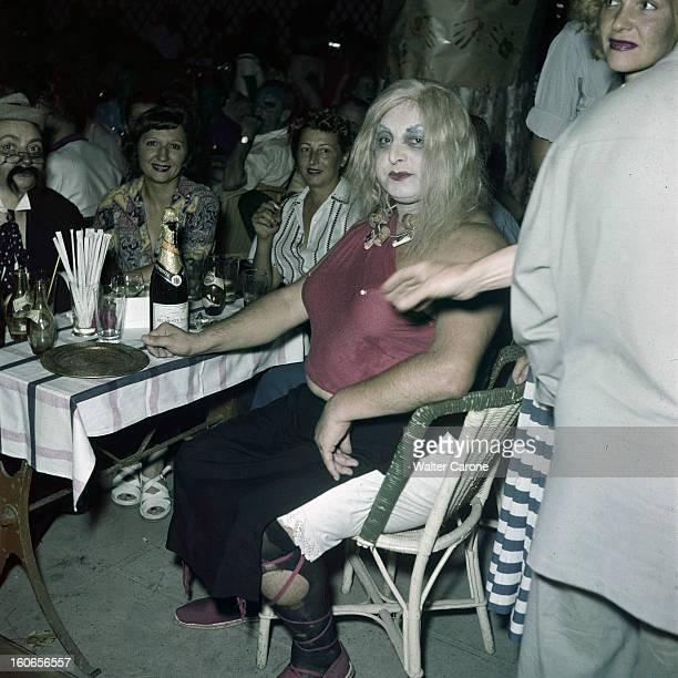 Popular Ball Costume In Juan Les Pins Juan les Pins Bal costumé populaire homme déguisé en travesti assis à une table