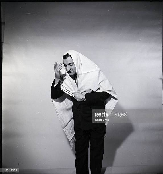 Popular fifities television actor Danny Thomas emotes from under a bed sheet