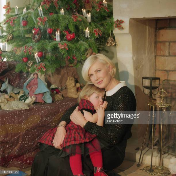 Popular French singer Michele Torr hugs her young daughter Charlotte next to the fireplace in their living room They are sitting next to a Christmas...