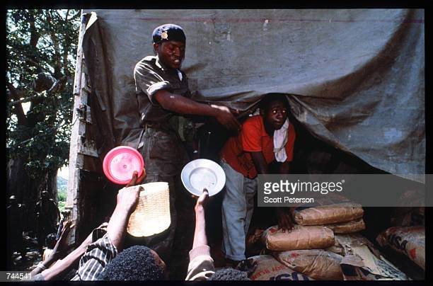 Popular Liberation Movement of Angola soldier unloads food from United Nations convoy March 24 1993 in Caimbambo Angola Despite a 1991 peace treaty...