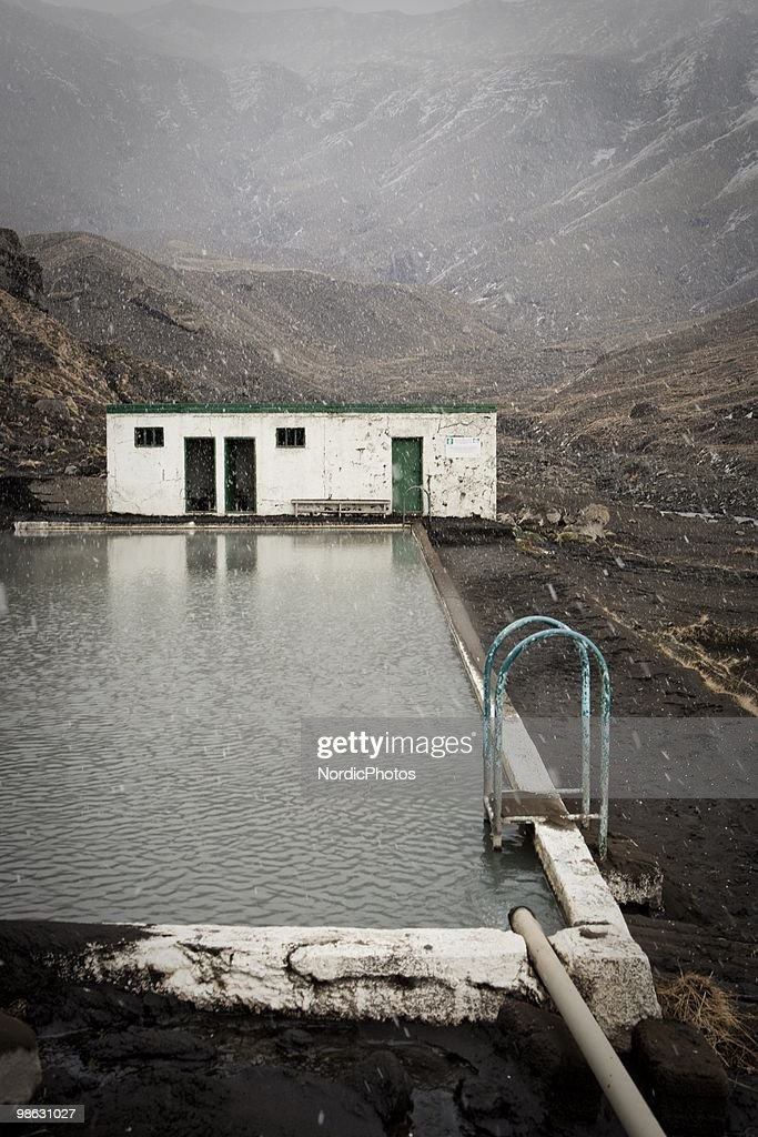 A popular tourist attraction for mountain climbers, Seljavallalaug, a swimming pool in a valley in the Eyjafjoll mountain range is covered by a thick layer of ash from the Eyjafjallajokull, on April 21, 2010 in Skogar, Iceland. The ash is killing nearby pasture and polluting water supplies which is poisoning animals and is causing farmers severe financial difficulties.