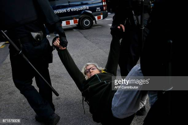 Popular Unity Candidacy member Maria Jose Lecha i Gonzalez is dragged by Catalan regional policemen at a picket blocking the street at the bus North...