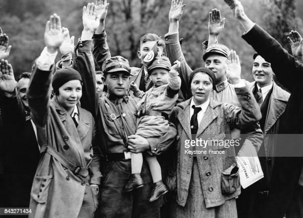 Population allemande dont un membre des SA faisant le salut nazi lors d'un défilé en Allemagne circa 1933