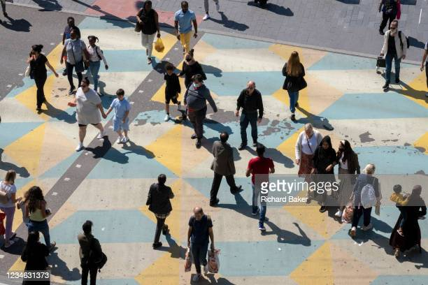Population of diverse and ethnic shoppers and other pedestrians cross the road in Stratford, on 11th August 2021, in London, England.