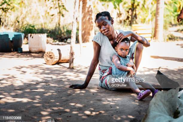 porait of a young african woman seated with her baby - malnutrition stock pictures, royalty-free photos & images
