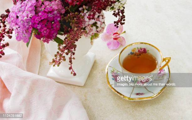 a porcelain cup of the tea with a white vase with flowers and a pink shawl. still life. - porcelain stock pictures, royalty-free photos & images